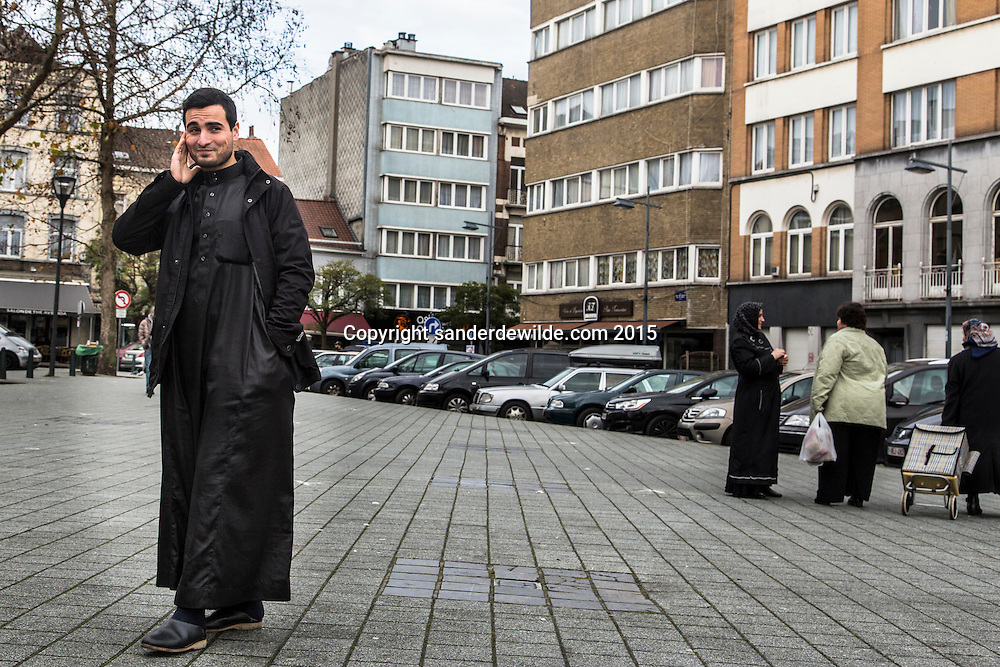 Belgium, Brussels, Sint Jans Molenbeek. 12 December 2015.  Molenbeek, the community of Brussels where terrorists of the Paris attacks lived. A young Imam poses for a portrait on the parvis st. Baptist after being interviewed. Women talk in the background. (Sander de Wilde for National Post)(For story by Matthew Fischer, foreign correspondent)(Sander de Wilde for National Post)(For story by Matthew Fischer, foreign correspondent)
