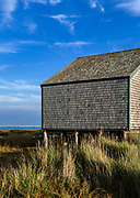 Nauset Marsh salt pond and rustic boathouse leading out to Cape Cod National Seashore, Eastham, Cape Cod, Massachusetts, USA.