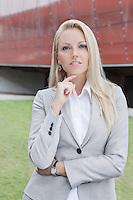 Portrait of confident businesswoman gesturing against office building