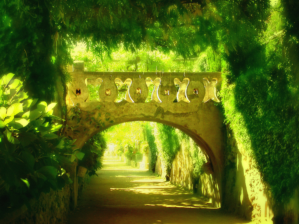 The gardens of Villa Cimbrone in Italy with small decorative bridge over path with strong sunlight through trees