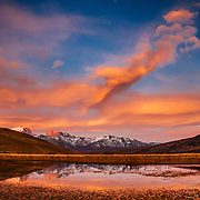The sun rises over the Towers of Paine in Torres del Paine National Park, Chile with heavy lenticular clouds building.