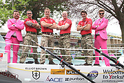 Michael Shinners from Sky Bet (left) and Racing UK presenter Tom Stanley (right) dressed in their pink suits pose with the Row 4 Victory Team in at York Racecourse, York, United Kingdom on 13 July 2018. Picture by Mick Atkins.