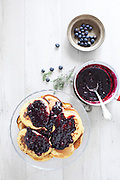 Breakfast table with blueberry cakes garnished with blueberries jam.
