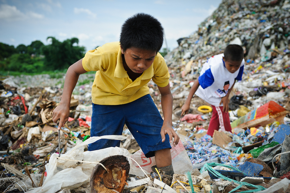Taupik (l), 14, and Idris, 13, collecting plastic and metal waste for recycling at the 'Trash mountain', Makassar, Sulawesi, Indonesia.