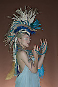 Portrait of young woman in feathered outfit over colored background