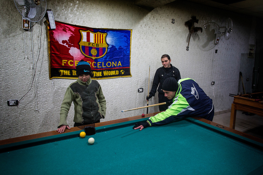 Kids play pool at a café in Aleppo.