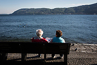 VERBANIA, ITALY - 18 APRIL 2017: Two elderly people relax on a bench by the Lake Maggiore in Verbania, Italy, on April 18th 2017.<br /> <br /> Emma Morano was an Italian supercentenarian who, prior to her death at the age of 117 years and 137 days, was the world's oldest living person whose age had been verified, and the last living person to have been verified as being born in the 1800s. She died on April 15th 2017.