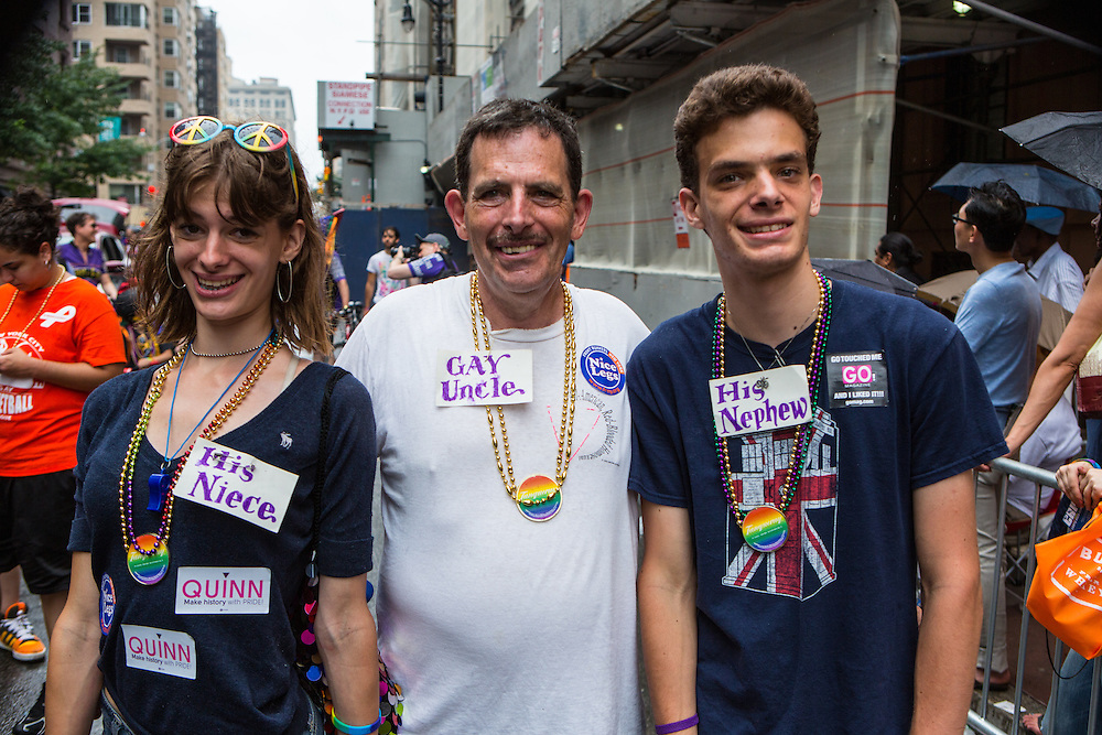 "A man wears a tag that reads ""Gay Uncle"" while a young woman wears a tag reading ""His niece"" and a young man wears one reading ""His nephew."""