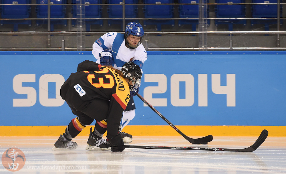 Feb 16, 2014; Sochi, RUSSIA; Finland forward Linda Valimaki (10) controls the puck against Germany defenseman Tanja Eisenschmid (23) in the women's ice hockey classifications round during the Sochi 2014 Olympic Winter Games at Shayba Arena.