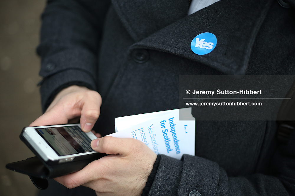 GLASGOW, SCOTLAND - MARCH 14:  Patrick Grady, a pro-Scottish independence campaigner for Yes Scotland, stands using Twitter social media app on his smartphone whilst canvassing on March 14, 2014 in Partick district, Glasgow, Scotland. A referendum on whether Scotland should be an independent country from the United Kingdom will take place on September 18, 2014.  (Photo by Jeremy Sutton-Hibbert/Getty Images)