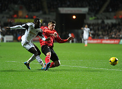 Swansea City's Nathan Dyer gets the ball across the box under pressure from Cardiff City's Declan John - Photo mandatory by-line: Alex James/JMP - Tel: Mobile: 07966 386802 08/02/2014 - SPORT - FOOTBALL - Swansea - Liberty Stadium - Swansea City v Cardiff City - Barclays Premier League