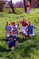 While in in period costumes, Kristin Norris in front leads (L-R) Erin Norris, Karen Norris, Emily Price and Sarah Price down the grassy hill at Marshall Gold Discovery State Park Sat. March 25, 2000. The children are all from Placerville and volunteer at the park. Saturday was the Sarah's  Quilting Party, a womans rights suffrage march, part of womans history month. On the hill is Adrienne Norris, watching the other children..
