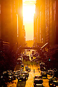 View of the sunset on 42nd Street in Manhattan, New York City during summer. Pedestrians, vehicles and traffic can be seen silhouetted by the sun.