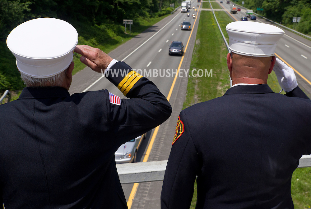 Monroe, New York - Members of the Mombasha Fire Company salute as the  procession carrying Army Capt. Jason B. Jones passes by on Route 17 on the from Pennsylvania to funeral services at West Point on June 74, 2014.  Jones was killed in Afghanistan on June 2, 2014.
