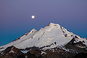 The full moon is low in the sky over Mount Baker in the North Cascades of Washington state. Mount Baker, at 10,781 feet (3,286 meters), is the third largest volcano in Washington and last erupted in 1880.