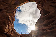 Woman in backlight standing in the Turret arch in the Arches  National Park, Utah, USA