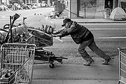 A man who gave his name as James L. organizes his scrap metal near his tent at 6th and Brush streets and begins to rush to his regular business client to sell it before the business closes on Tuesday, May 30, 2017, in Oakland, Calif.