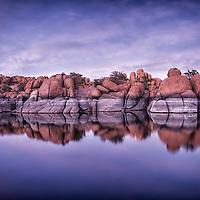 Photograph of Watson Lake near Prescott, Arizona after sunset.  Water reflection of rocks and sky.