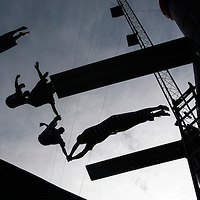 Performers in a high dive act fly through the air as they plunge toward their 9 1/2-foot-deep tank Sept. 8, 2007, at the fairgrounds in Odessa, Texas.
