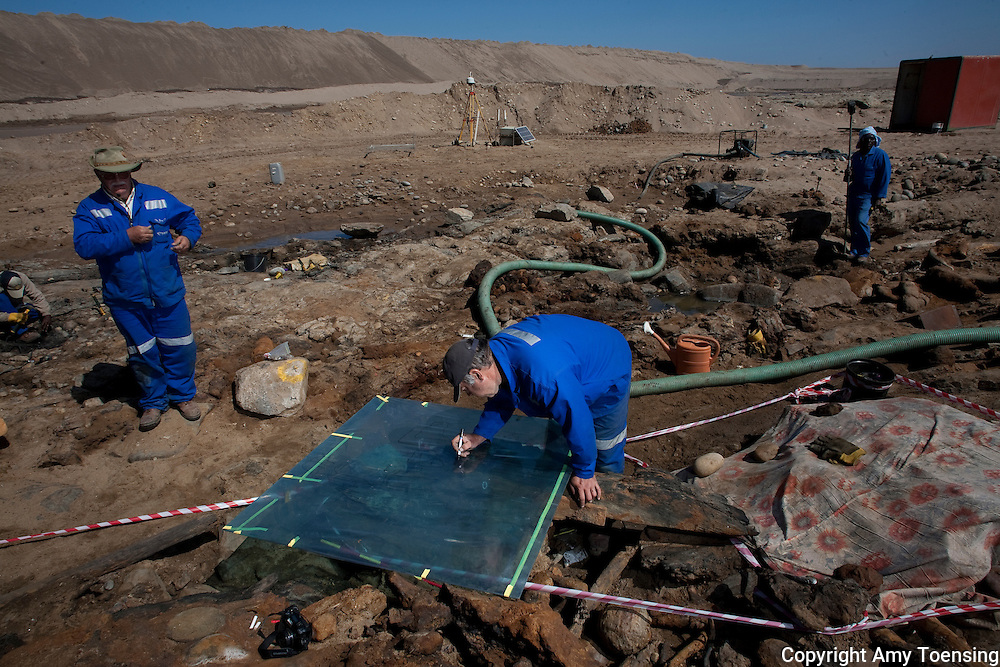 ORANJEMUND, NAMIBIA -- OCTOBER 04: Archeologists outline the position of the artifacts before removing them from on site October 04, 2008 in Oranjemund, Namibia. The wreck was uncovered by miners in the Namdeb diamond mine off the coast of Namibia. The ship was found seven meters below sea level on April 1, 2008. Archeologists presume the wreck is from the early 1500s. Most of the the artifacts found are being stored in a storage shed at the Namdeb Diamond Mine. Items include: copper ingots, bronze canons, canon balls, pewter bowls and plates, ivory tusks from African elephants, and most substantial over 2000 gold coins- approximately 21 kg - the most gold found in Africa since the Valley of the Kings in Egypt. (Photo by Amy Toensing) _________________________________<br />