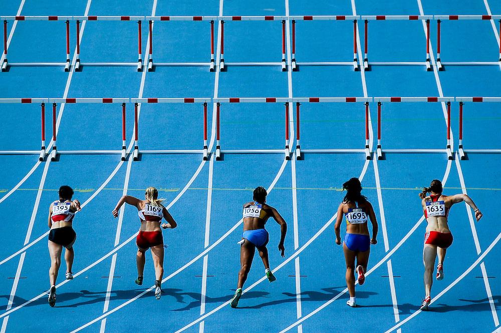 Atletas toman la salida en su serie de clasificación en los 100 metros vallas durante el cuarto día de los 14º IAAF Mundiales Junior de Atletismo en el Estadio Olímpico Lluis Companys de Barcelona, España el 13 de Julio del 2012.