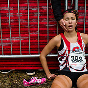 Shorewood senior Hayley Floresheim (393) collapses against a fence while her mother comforts her after finishing the WIAA Division 2 Girls Cross Country Tournament at Ridges Country Club in Wisconsin Rapids, Wis., on November 2, 2013.  Lukas Keapproth/Press Gazette Media
