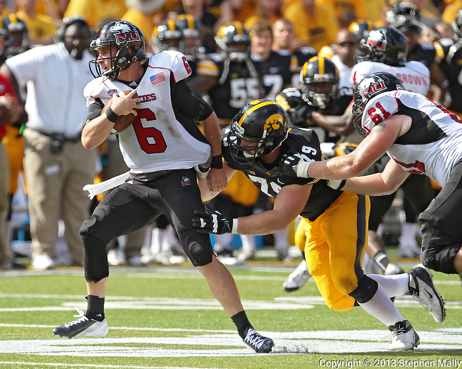August 31 2013: Northern Illinois Huskies quarterback Jordan Lynch (6) is pulled down by Iowa Hawkeyes defensive lineman Dominic Alvis (79) during the second quarter of the NCAA football game between the Northern Illinois Huskies and the Iowa Hawkeyes at Kinnick Stadium in Iowa City, Iowa on August 31, 2013. Northern Illinois defeated Iowa 30-27.