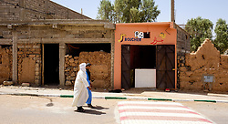 Two men in traditional dress walking past a butchers shop front in Mhamid, Morocco<br /> <br /> (c) Andrew Wilson | Edinburgh Elite media