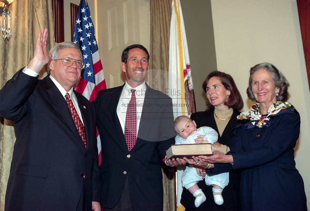 Speaker of the House Denis Hastert (L) administers the oath of office to Rep. Mark Sanford of South Carolina as his wife Jenny and family looks on January 6, 1999 at the start of the 106th Congress. The oath is a recreation as the formal oath is administered to the entire congress as a body on the floor of the House.
