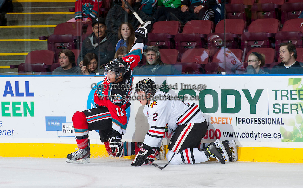 KELOWNA, CANADA - OCTOBER 4:  Tyrell Goulbourne #12 of the Kelowna Rockets collides with Anton Cederholm #2 of the Portland Winterhawks  at the Kelowna Rockets on October 4, 2013 at Prospera Place in Kelowna, British Columbia, Canada (Photo by Marissa Baecker/Shoot the Breeze) *** Local Caption ***