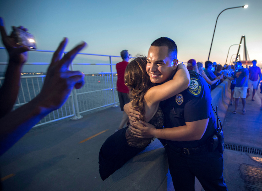 Mt. Pleasant Police Officer Brandon Montano gets high-fives and hugs from some of the thousand of people walking along the Arthur Ravenel Jr. Bridge during a Hands Across The Bridge event, Sunday, June 21, 2015, in Charleston, S.C. The Ravenel Bridge joins Charleston and Mt Pleasant. (AP Photo/Stephen B. Morton)