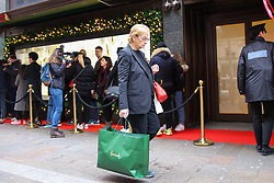 © Licensed to London News Pictures. 26/12/2018. London, UK. A woman walks past with a Harrods shopping bag as <br /> shoppers queue outside the luxury department store Harrods in Knightsbridge ahead of the opening of the Boxing Day sale. Boxing Day is one of the busiest days for retail outlets with tens of thousands of shoppers taking advantage of the post-Christmas bargains. Photo credit: Dinendra Haria/LNP