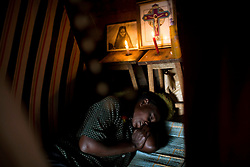 Consolata Anyango, 39, who has HIV and TB, rests on the dirt floor of her small hut surrounded by pictures of figures from her church, Legion Maria, in Mathare, one of the poorest slums in Nairobi.  Running water and electricity are scarce and trash and human waste fills the streets.  Many people have no jobs and those who do work can earn less than one dollar a day.