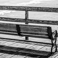 Seal Beach California pier bench and railing black and white photo. Seal Beach is in Orange County Southern California in the United States of America. Panoramic photo ratio is 1:3.
