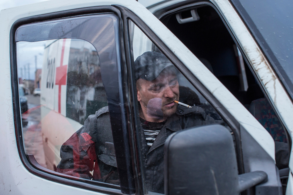 Yevgeny Kishkin, age 31, from Kakhovka in the Kherson region, a member of the Black Tulips, with the vehicle used to collect unclaimed bodies on Wednesday, April 9, 2015 in Velyka Novosilka, Ukraine.