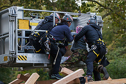 London, UK. 9 October, 2019. Police officers use a JCB cherry picker to arrest one of several climate activists from Extinction Rebellion who had climbed on top of a wooden structure to block Birdcage Walk on the third day of International Rebellion protests.
