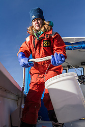 Ivy Frignoca, Casco Baykeeper, water testing from boat in Casco Bay in winter