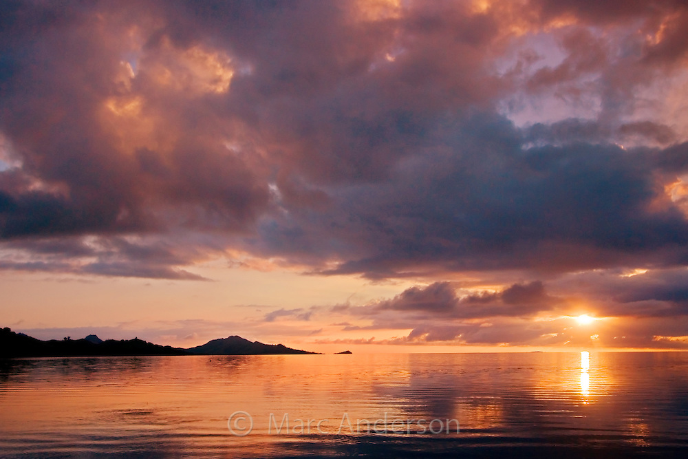 A cloudy sunset over the sea off a tropical island in Fiji.