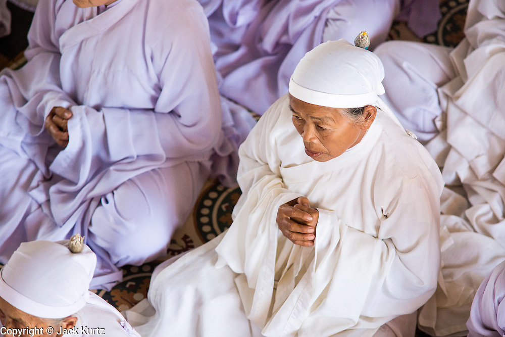 "29 MARCH 2012 - TAY NINH, VIETNAM:  Cao Dai adherents, in white, during noon services at the Cao Dai Holy See in Tay Ninh, Vietnam. Cao Dai (also Caodaiism) is a syncretistic, monotheistic religion, officially established in the city of Tây Ninh, southern Vietnam in 1926. Cao means ""high"" and ""Dai"" means ""dais"" (as in a platform or altar raised above the surrounding level to give prominence to the person on it). Estimates of Cao Dai adherents in Vietnam vary, but most sources give two to three million, but there may be up to six million. An additional 30,000 Vietnamese exiles, in the United States, Europe, and Australia are Cao Dai followers. During the Vietnam's wars from 1945-1975, members of Cao Dai were active in political and military struggles, both against French colonial forces and Prime Minister Ngo Dinh Diem of South Vietnam. Their opposition to the communist forces until 1975 was a factor in their repression after the fall of Saigon in 1975, when the incoming communist government proscribed the practice of Cao Dai. In 1997, the Cao Dai was granted legal recognition. Cao Dai's pantheon of saints includes such diverse figures as the Buddha, Confucius, Jesus Christ, Muhammad, Pericles, Julius Caesar, Joan of Arc, Victor Hugo, and the Chinese revolutionary leader Sun Yat-sen. These are honored at Cao Dai temples, along with ancestors.    PHOTO BY JACK KURTZ"