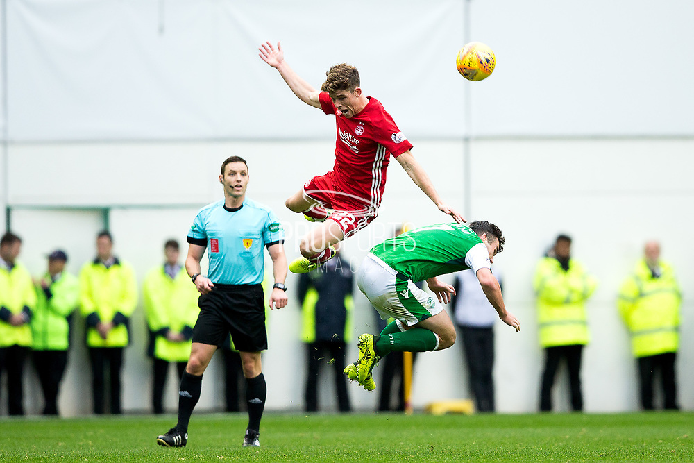 Aberdeen midfielder Ryan Christie (#22) leaps above Hibernian midfielder John McGinn (#7) to win a header during the Ladbrokes Scottish Premiership match between Hibernian and Aberdeen at Easter Road, Edinburgh, Scotland on 14 October 2017. Photo by Craig Doyle.