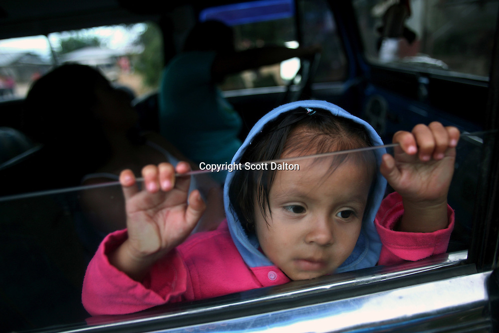 A young girl looks out the window of a car in El Ofrio, a small remote village in the southern Colombian state of Nariño, on Saturday, June 23, 2007. There are coca fields located in the vicinity of El Ofrio, but the residents know that soon fumigation and manual eradication of their coca crops by the Colombian government will force them to find a new means to earn cash. (Photo/Scott Dalton)