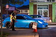 Bellmore, New York, USA. August 11, 2017.  Members of the Chamber of Commerce of the Bellmores wear yellow neon reflective safety vests as they guide cars into the main lot of the Long Island Rail Road Bellmore Train Station parking lot where the Bellmore Friday Night Car Show is held.