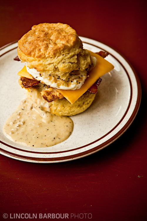 The Reggie Deluxe: Egg, Bacon, Cheddar Cheese, Fried Chicken, on a Biscuit covered in Sausage Gravy