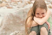 Pensive girl (10-12) sitting on rock on beach