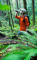Man in forest drinking from water bottle.