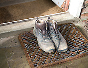 A pair of muddy old walking boots on a mat outside a doorway