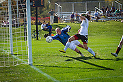 Patty Murphy-Geiss '14, right, attempts to kick a short shot in past Coe College goalkeeper Jillian Reynolds '14 in the second half of Sunday's 1-0 overtime victory on Springer Field.