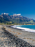 Waves crash on the the cobble-covered Kaikoura Beach with clouds over the Kaikoura Range in the background.