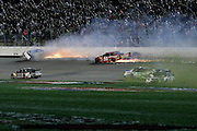 Alex Bowman (23) slips past while drivers spin into the infield as David Gilliland, top left, and Justin Allgaier (51) hit the wall during a NASCAR Sprint Cup Series auto race at Kansas Speedway in Kansas City, Kan., Saturday, May 10, 2014. (AP Photo/Colin E. Braley)