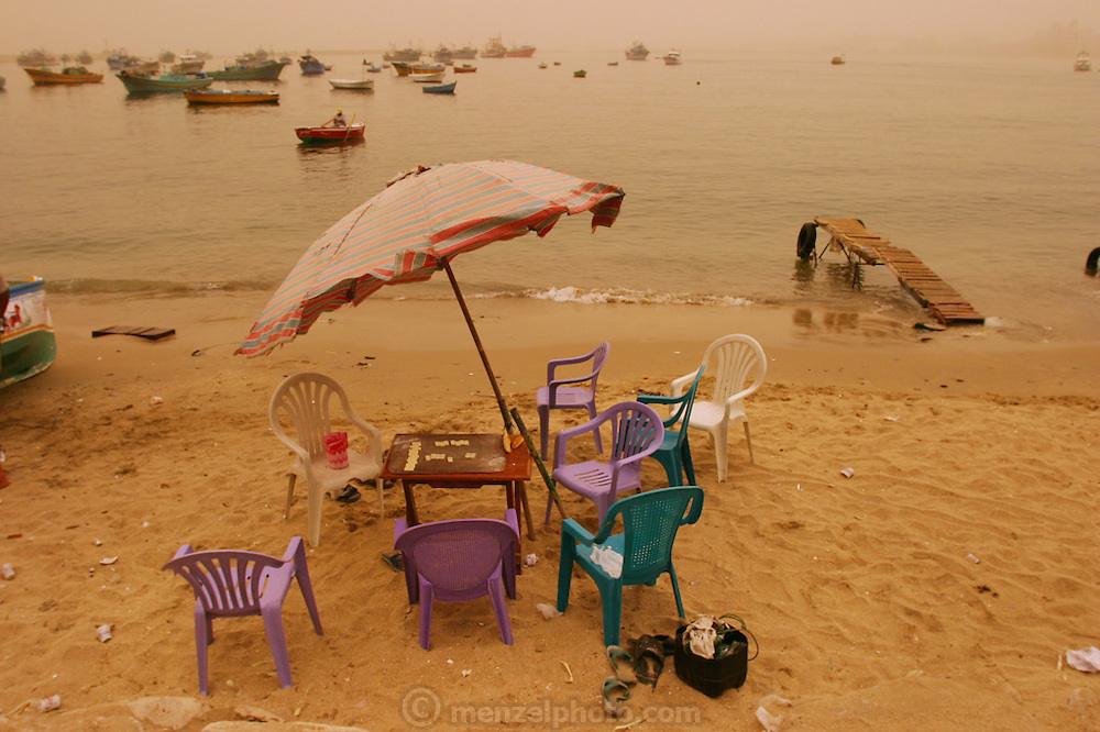 The beach at the port of Alexandria, Egypt during a sandstorm. The yellow-orange light is from the sand in the sky filtering the sunlight.